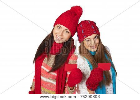 Two girls in winter clothing showing credit cards