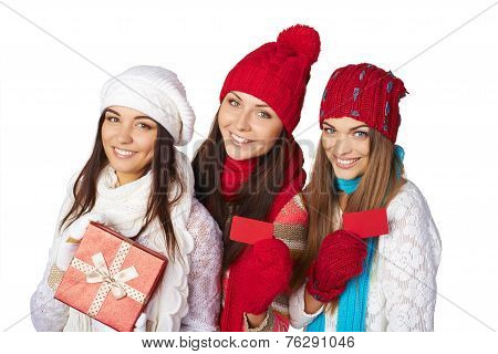 Three girls in winter clothing showing credit cards