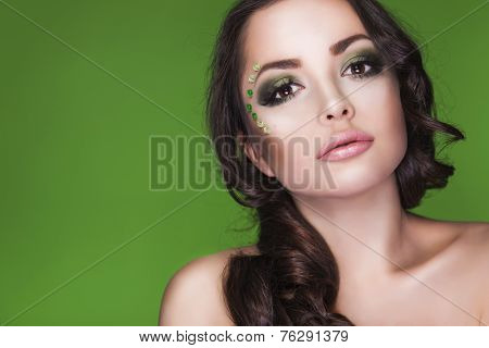 Beautiful brunette dryad woman with creative make up and beads on her face, curly hair and costume m