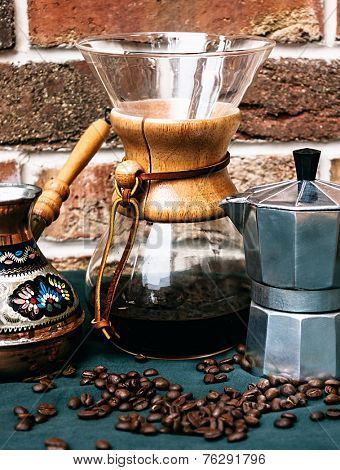 Close up Black Coffee Maker and Containers on Green Table with Coffee Beans