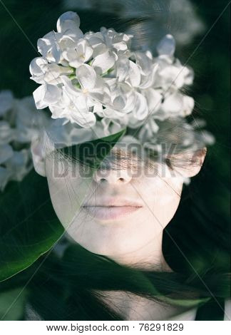 Dream like double exposure portrait of young woman combined with photograph of white lilac flowers