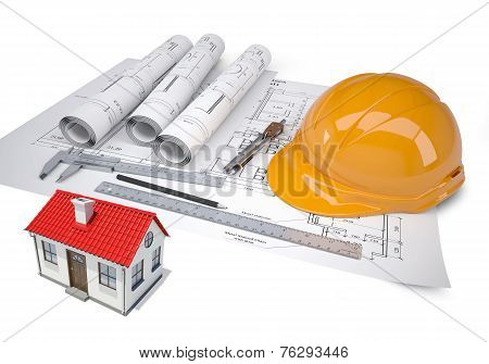 Small model house with red roof near architectural drawings and work tools