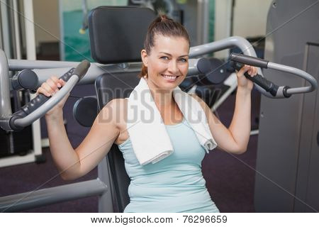 Fit brunette using weights machine for arms at the gym
