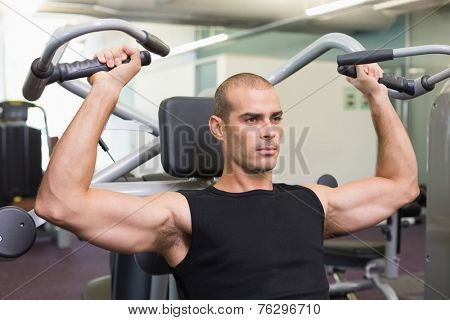 Portrait of a serious young man working on fitness machine at the gym