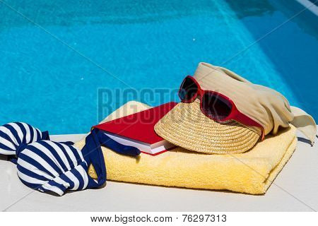 utensils for a nice and relaxing vacation day lying next to a swimming pool. relaxation on holiday.
