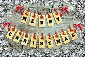 stock photo of pegging  - Merry Christmas lettering with clothes - JPG