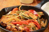 image of poblano  - Closeup of chicken asada in a cast iron skillet - JPG