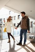 image of leaving  - Young couple leaving apartment house with small luggage - JPG