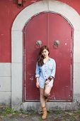 stock photo of filipina  - Asian woman in front of traditional Chinese door with ornate lion head knockers - JPG