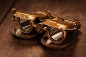 picture of voyeur  - Vintage opera glasses binoculars on old wooden background - JPG