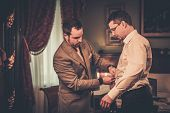 stock photo of tailoring  - Tailor measuring client for custom made suit tailoring  - JPG