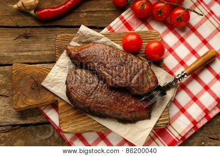 Composition with tasty roasted meat on cutting board, tomatoes and rosemary sprigs on wooden background