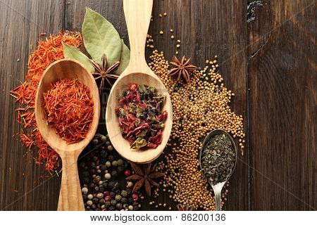 Different kinds of spices in spoons, close-up, on wooden background