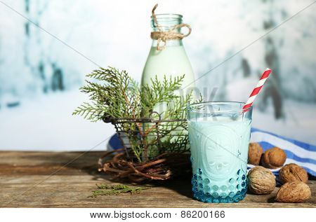 Fresh milk with natural decor, on wooden table, on winter background