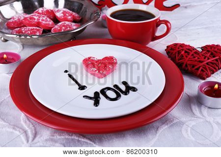 Cookie in form of heart on plate with inscription I Love You on color wooden table background