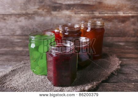Homemade jars of fruits jam on rustic wooden background