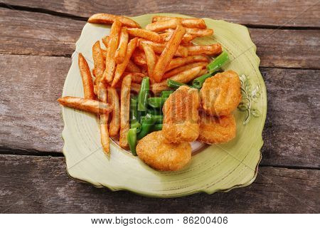 Breaded fried chicken nuggets and potatoes with asparagus on plate with napkin on wooden planks background