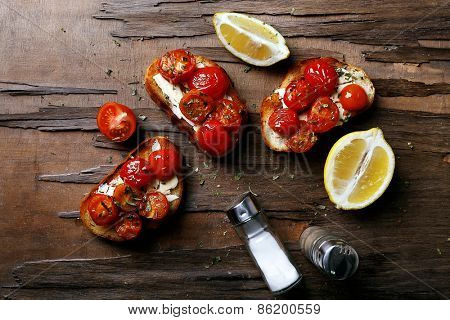 Slices of white toasted bread with canned tomatoes and lime on wooden table background