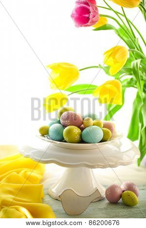 Easter eggs on vase and tulips on table on bright background