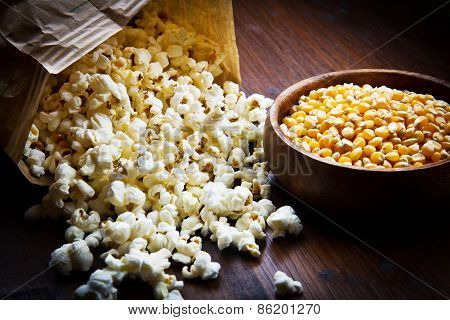 A Bowl Of Popcorn And Kernelson A Wooden Table