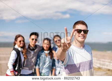 summer holidays and teenage concept - teenage boy in sunglasses hanging out with friends outside