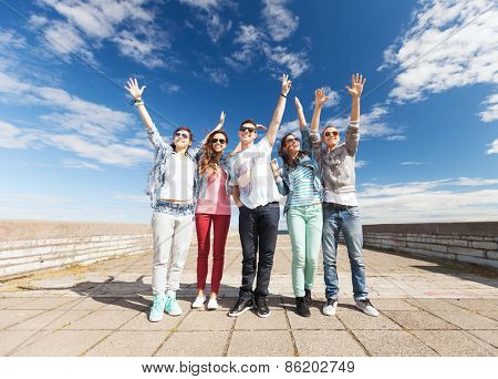 summer holidays and teenage concept - group of teenagers holding hands up outside