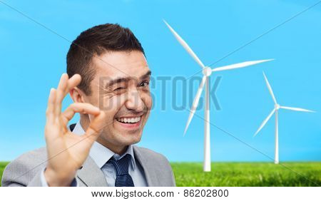 business, people, alternative energy and development concept - happy smiling businessman in suit showing ok hand sign over blue sky and windmills background