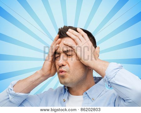 stress, headache, health care and people concept - unhappy man with closed eyes touching his forehead blue burst rays background