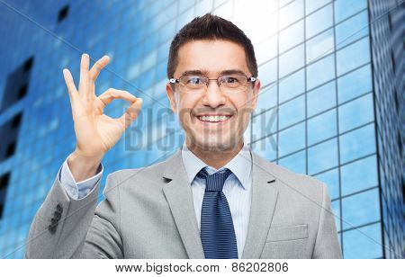 business, people, vision and success concept - happy smiling businessman in eyeglasses and suit showing ok sign over office building background