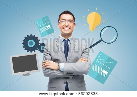 business, people, technology and development concept - happy smiling businessman in eyeglasses and suit over blue background and computer symbols