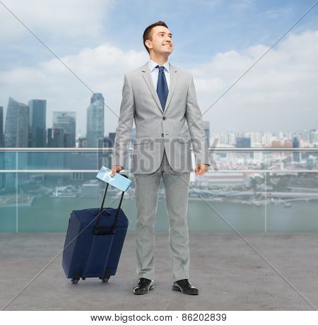 business trip, traveling, luggage and people concept - happy businessman in suit with travel bag and air ticket over city background