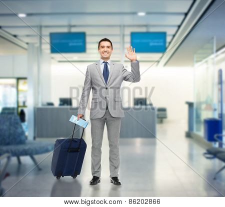 business trip, traveling, luggage and people concept - happy businessman in suit with travel bag and air ticket waving hand over airport background