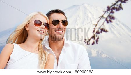 summer holidays and dating concept - couple in shades over japan mountains background