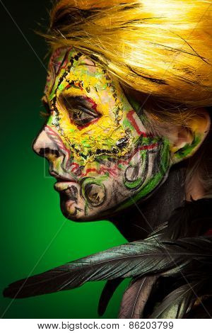 woman with face-art and body art paint. Yellow hair. Like bird.