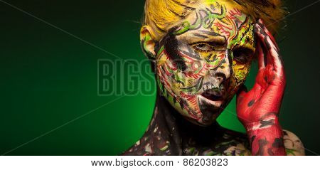 Woman posing in studio. Body and face art. Like bird.