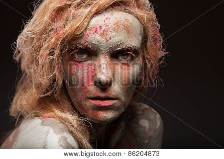 Portrait of a beautiful woman with her face covered with clay