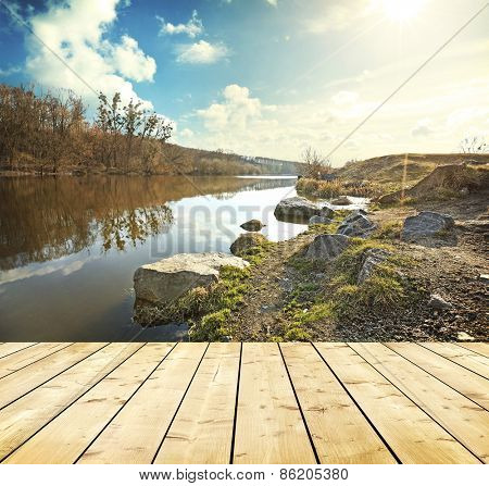 View of the river with green coast with stones and clouds and bright sun with floor from wooden planks