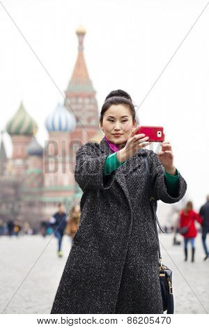 Young beautiful woman tourist taking pictures on mobile phone on the background Red Square, Moscow Kremlin, Russia