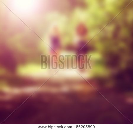 two girls riding bikes on a path in a park full of trees done with a retro vintage instagram filter effect app or action and blurred out so text can be place over the image