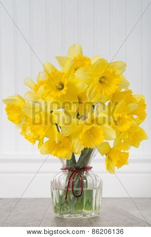 Daffodils In A Vase In Rustic Setting - Vertical