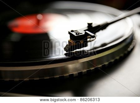 Close up view of old fashioned turntable playing a track from black vinyl.