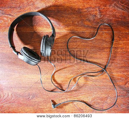 headphones and the cord in the shape of a heart symbolic of a love for music on an antique wooden texture background