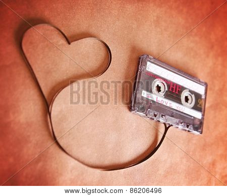 an old scratched up audio cassette tape in the shape of heart (focus on the words) on a brown paper texture background good for valentine's day or love greeting cards (SHALLOW DOF)