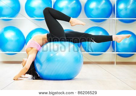 woman doing stretching on fitness ball during pilates exercises in sport club