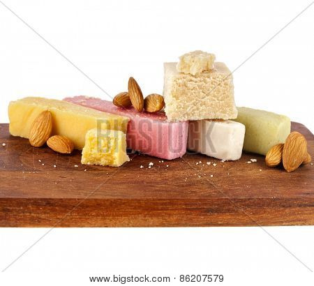 marzipan with almonds on wooden board close up isolated on white background