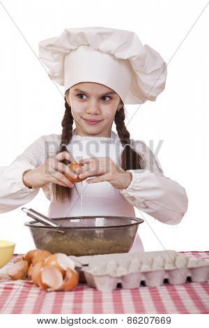 Little cook girl in a white apron breaks eggs in a deep dish, isolated on white background