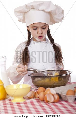 Little girl in a white apron breaks near the plate with eggs, isolated on white background