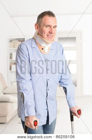 Standing man with crutches and cervical collar