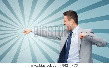 business, people and conflict concept - businessman in suit fighting with someone imaginary over blue burst rays background
