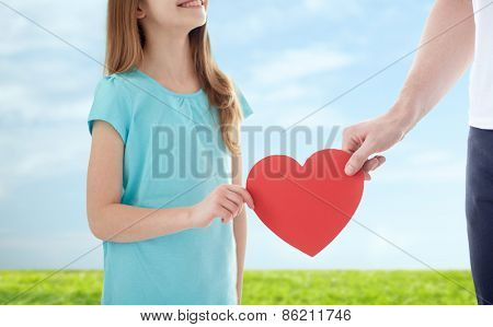 people, love, charity and family concept - close up of girl and male hand holding red heart shape over blue sky and grass background